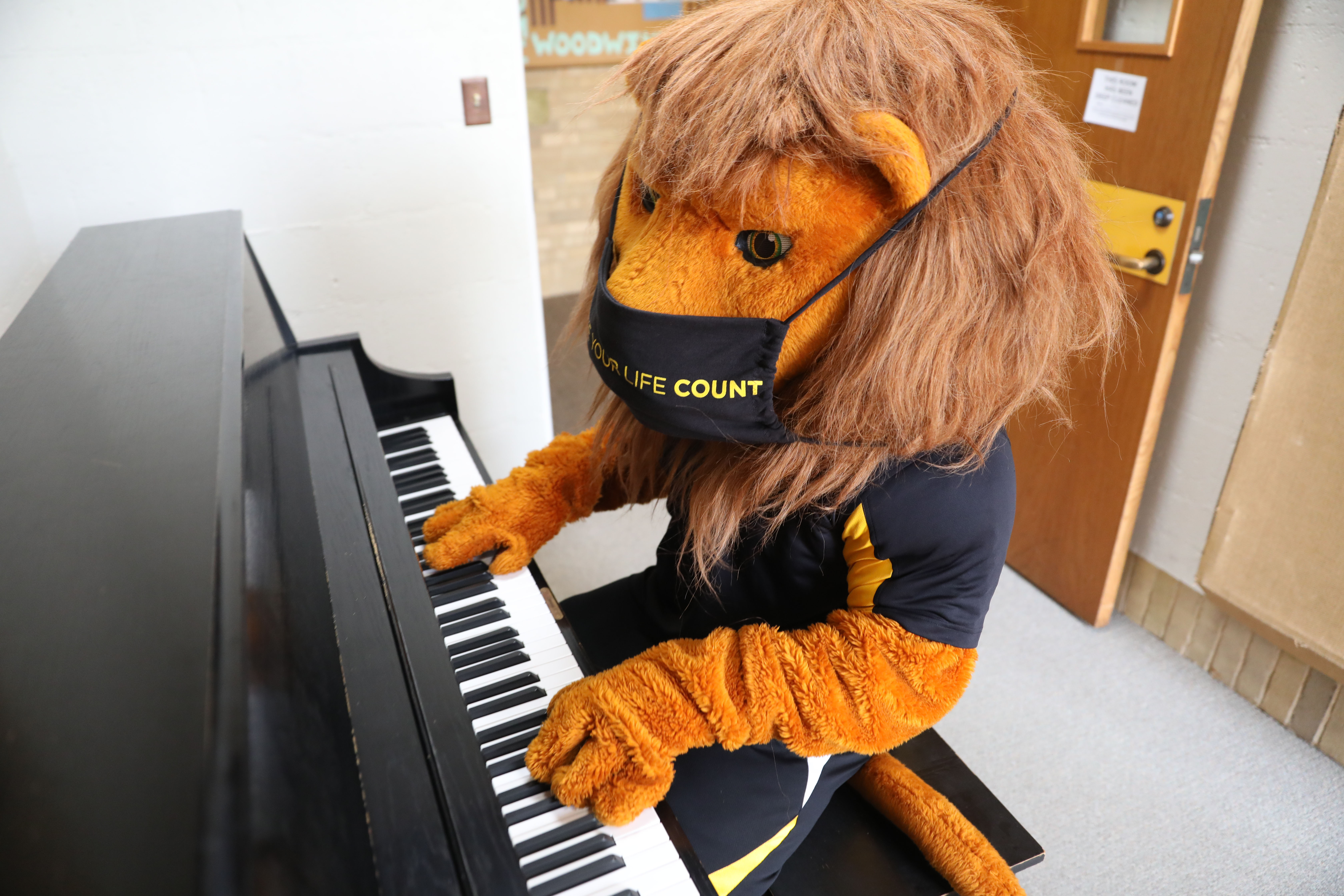Gus playing the piano with a mask