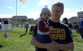 Photo 1: Young male dressed in black Gustavus shirt holds toddler while attending Gustavus Homecoming event Photo 2: Family dressed in Gustavus gear pose in silly props Photo 3: Photo of Gustavus Hollingsworth Football field with croweded stands full of fans