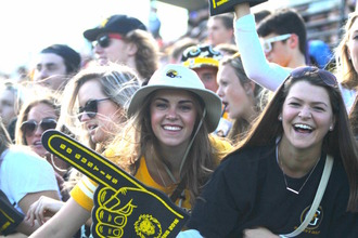 Gustie Greeters gather at the Gustavus sign all dressed in yellow and cheering