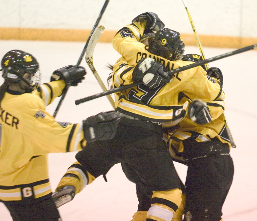 Kelly Crandall and Danny Blacker celebrate with two other teammates after the first of Gustavus' six goals.
