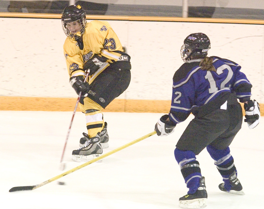 #23 Andrea Peterson slips the puck past the St. Thomas defender.