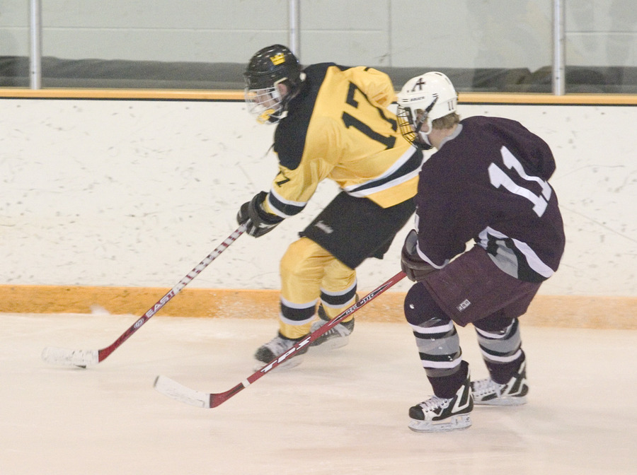 #17 Mike Hosfield keeps the puck away from the Auggie defender.
