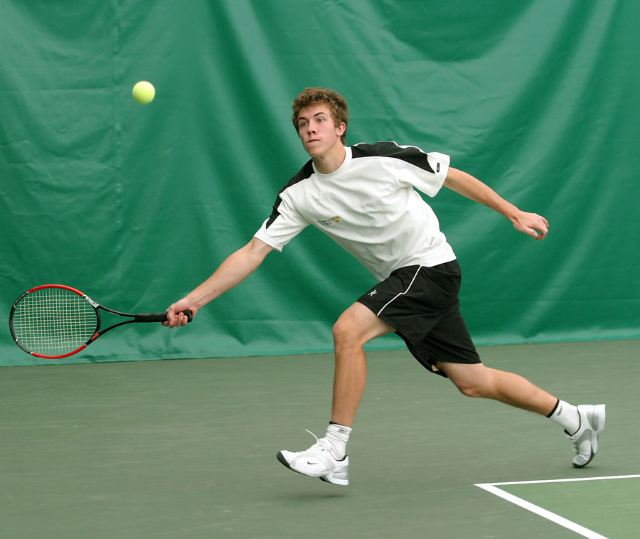 Freshman Andy Bryan stretches for a forehand return in the #3 doubles match.