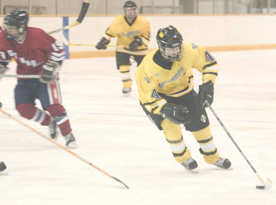 #4 Danny Blacker keeps the puck away from the Cardinal defenders.