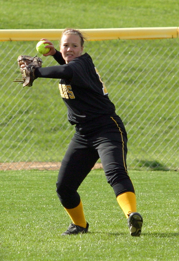 Left fielder Dawn Lewis returns  the ball to the infield after catching a fly ball.