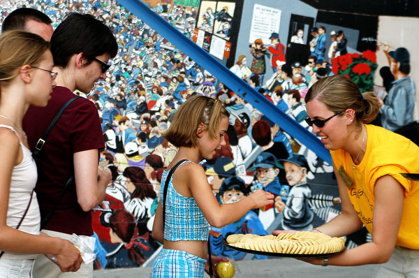 A Gustavus Ambassador passes out Gustavus three crowns cookies to young fans at a recent St. Paul Saints game.