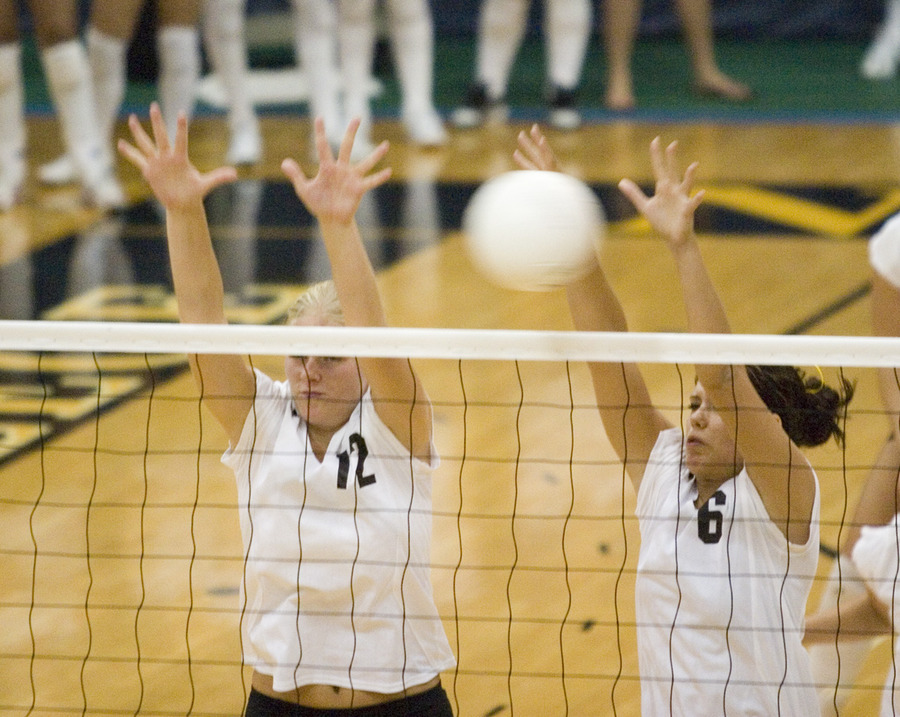 Jennifer Thelemann (l) and Becca Thompson (r) reach up for a block