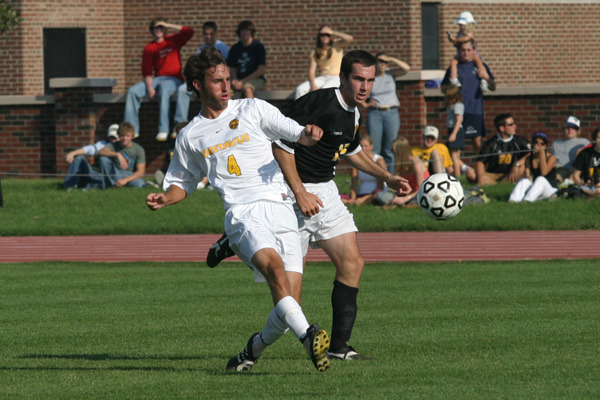 Jeff Aasness battles an opponent while clearing the ball