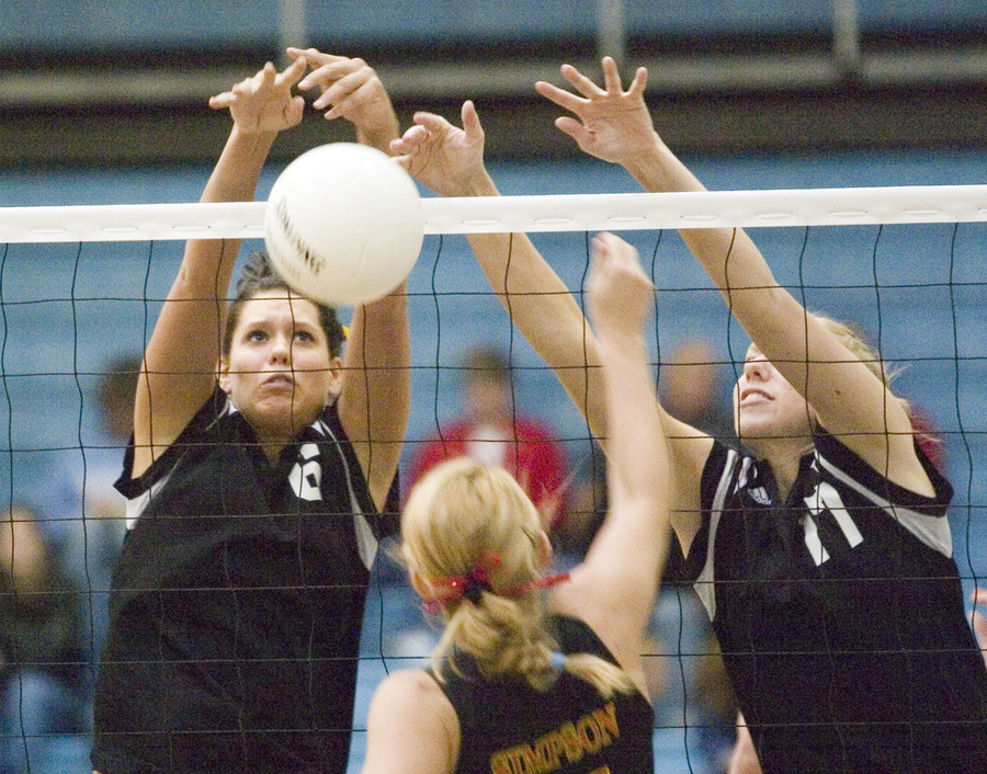 Becca Thompson (left) and Andrea Kron (right) reach for the block against Simpson