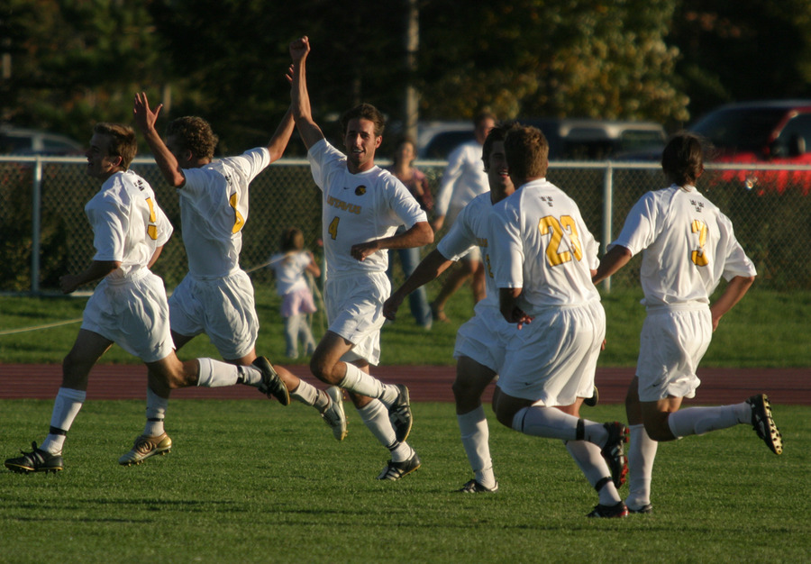 The Gustavus men's soccer team celebrates following a goal.