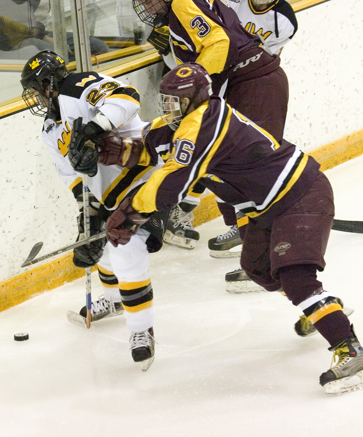 Steve Dusich (23) fights for the puck along the boards.