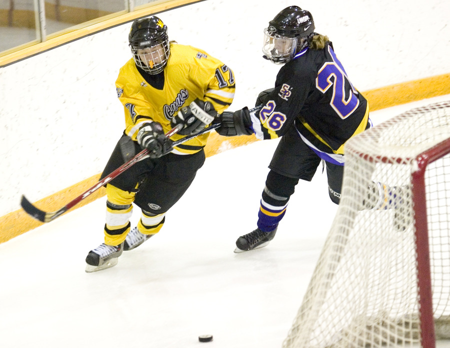 First-year Christine Wicker fights through the stick of Stevens Point's Rachael Graves