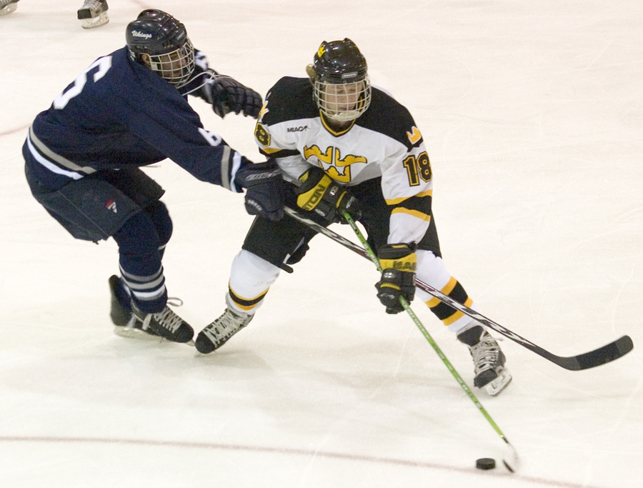 Junior John Arundel plays the puck just ahead of a Lawrence player.