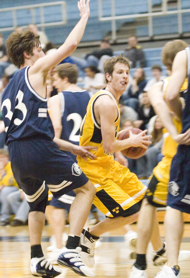 Robbie Schmidt attempts to drive to the hoop against Carleton's Tommy Drake.