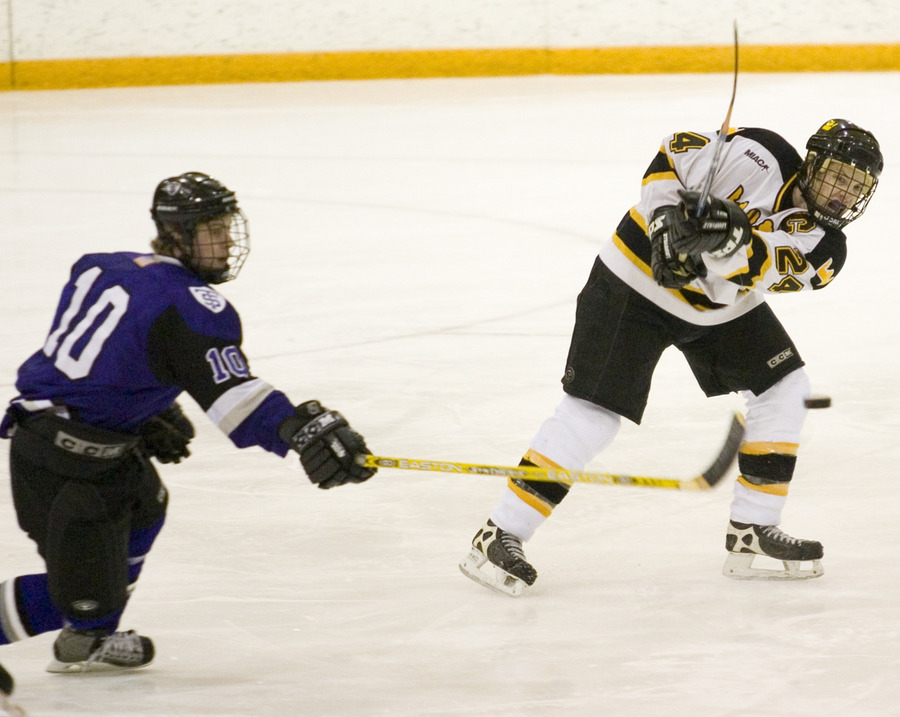 Jay Phillips shoots the puck in front of a Tommie.