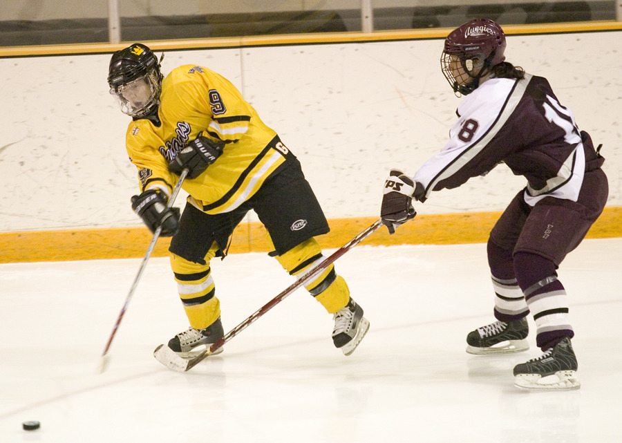Kelly Crandall passes the puck before an Auggie gets to her.