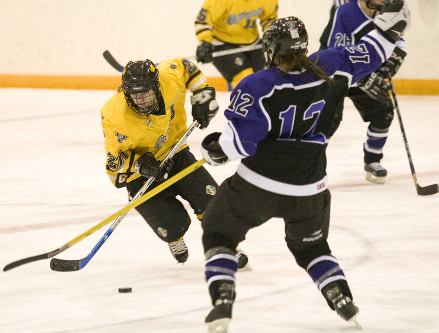 Molly Doyle skates with the puck while a Tommie is off balance.