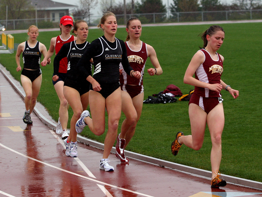 A Minnesota-Duluth runner leads Laura Edlund (r), Sarah Bernhardson (c) and Jill Fagerstrom (r) around a corner during the 5000.