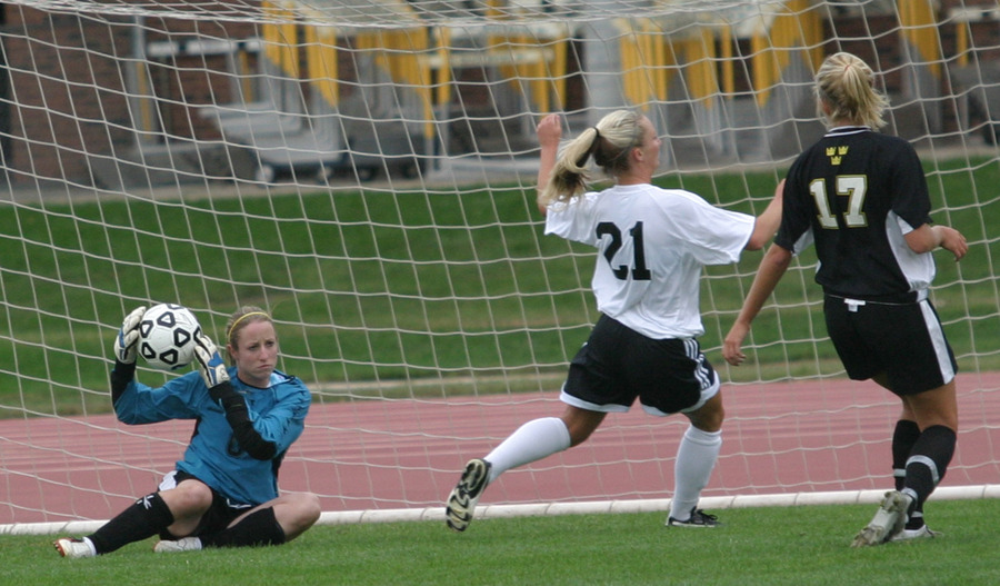 Julie Mahre makes a save as Alison Ditmer and a Nebraska Wesleyan player look on.