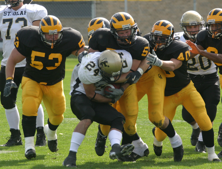 A crowd of Gustie defenders tackle a St. Olaf ball-carrier.