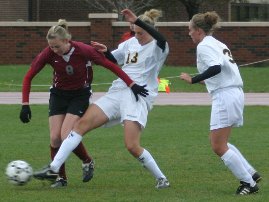 Jenna Iaizzo kicks the ball while under pressure from an Eagle.