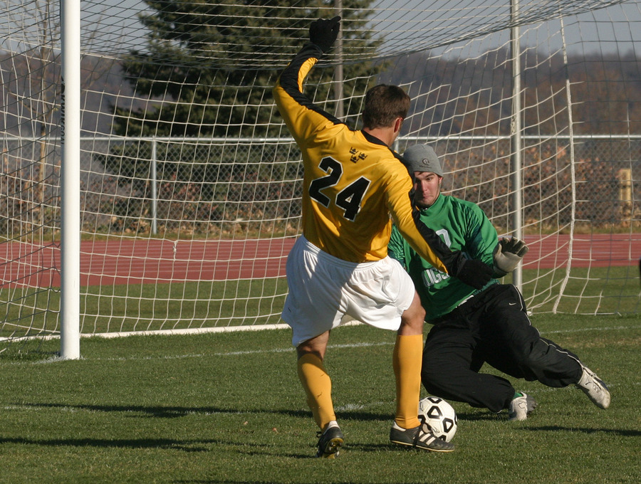 Alex Groth challenges goalkeeper Pascaul Venter by putting a shot on net.