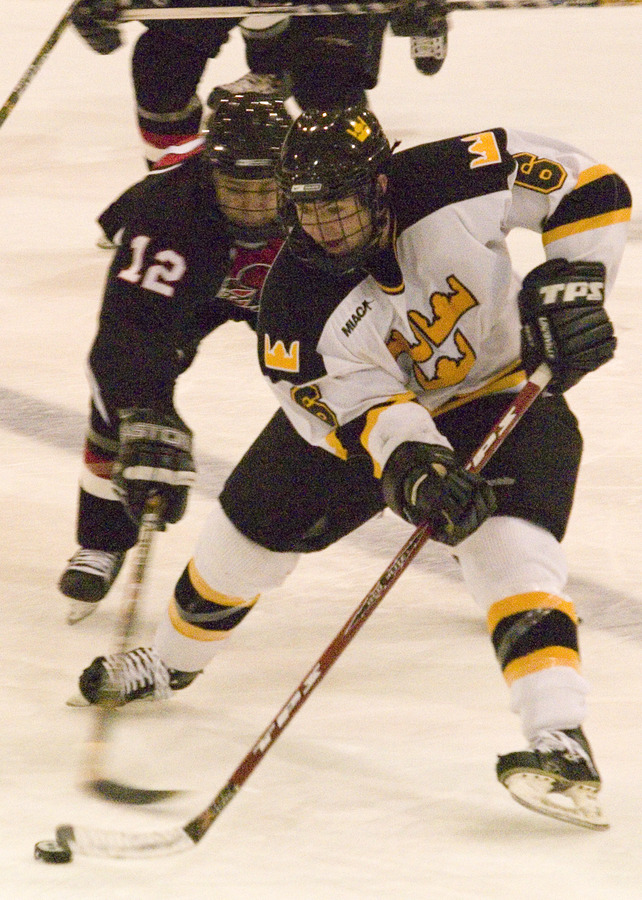 Cody Mosbeck tries to keep the puck away from a Falcon.