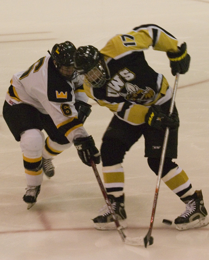 Freshman defenseman Cody Mosbeck battles with a UW-Superior defender for the puck.