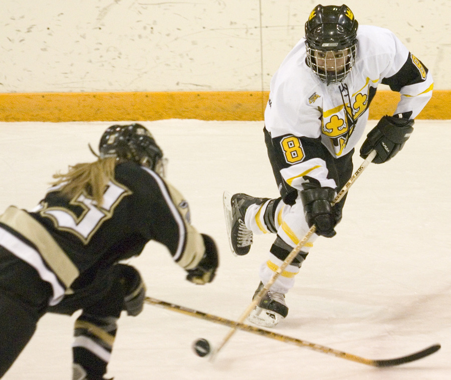 First year Melissa Mackley plays the puck past a St. Olaf defender.