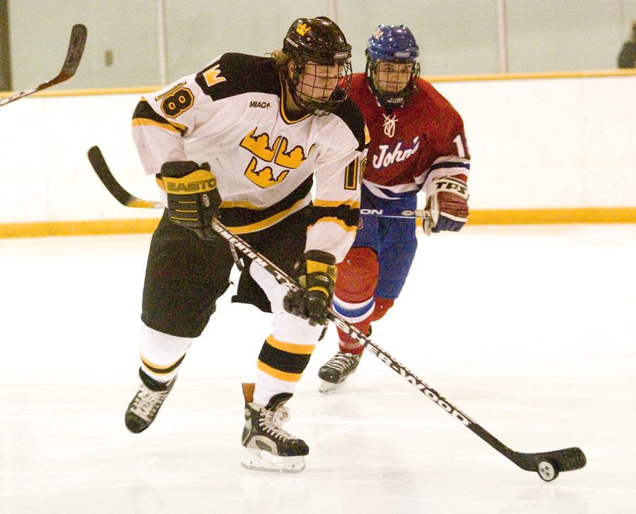 John Arundel carries the puck out of the Gustavus zone.