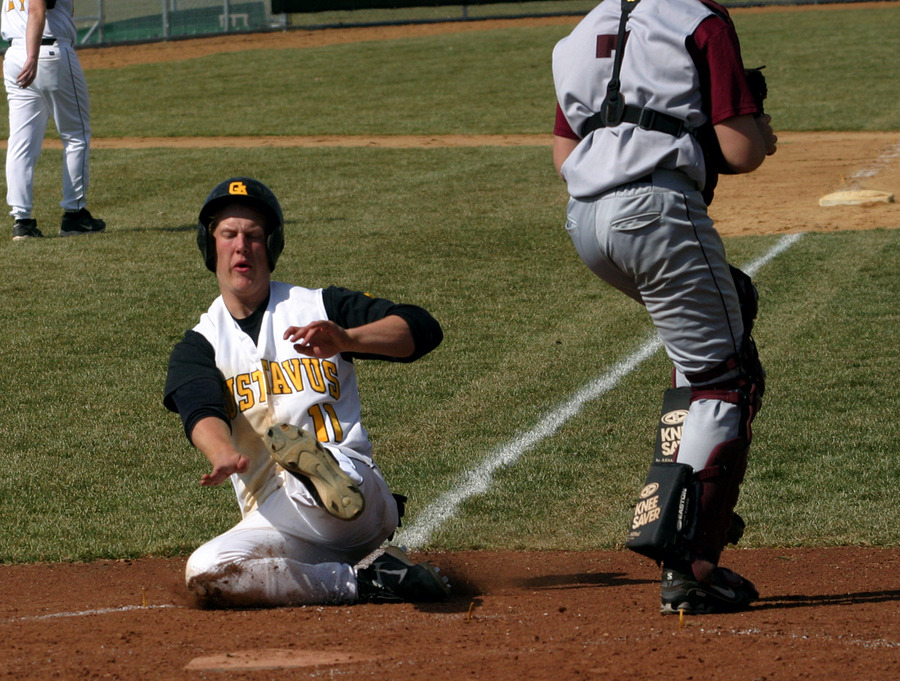 Freshman Spencer Campion slides into home plate behind the Augsburg catcher.