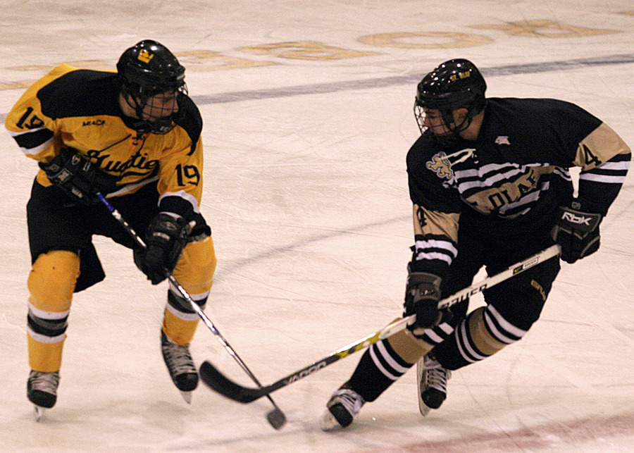 The Gusties Brad Wieck (#19) battles the Oles David Adams (#4) for control of the puck at center ice.