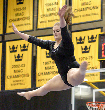 Emily Pickford performs a jump high above the balance beam.