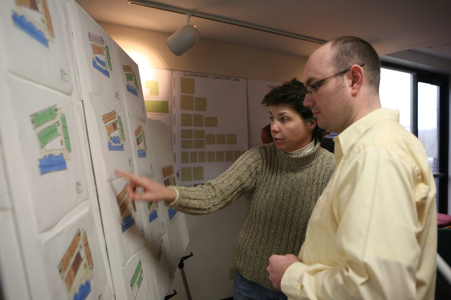 Communication Studies professors Leila Brammer and Kris Kracht look over architectural plans at a design workshop on April 10.