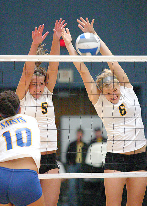 Britta Bolm and Meghan Gehring frustrate a St. Scholastica hitter.