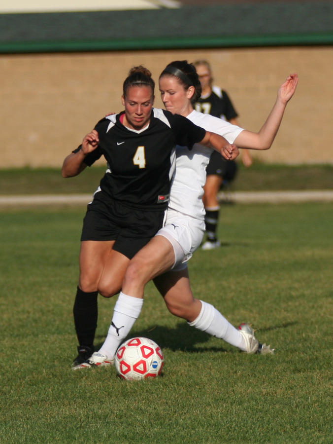 Callie Christensen battles a Cardinal player for possession in the midfield.