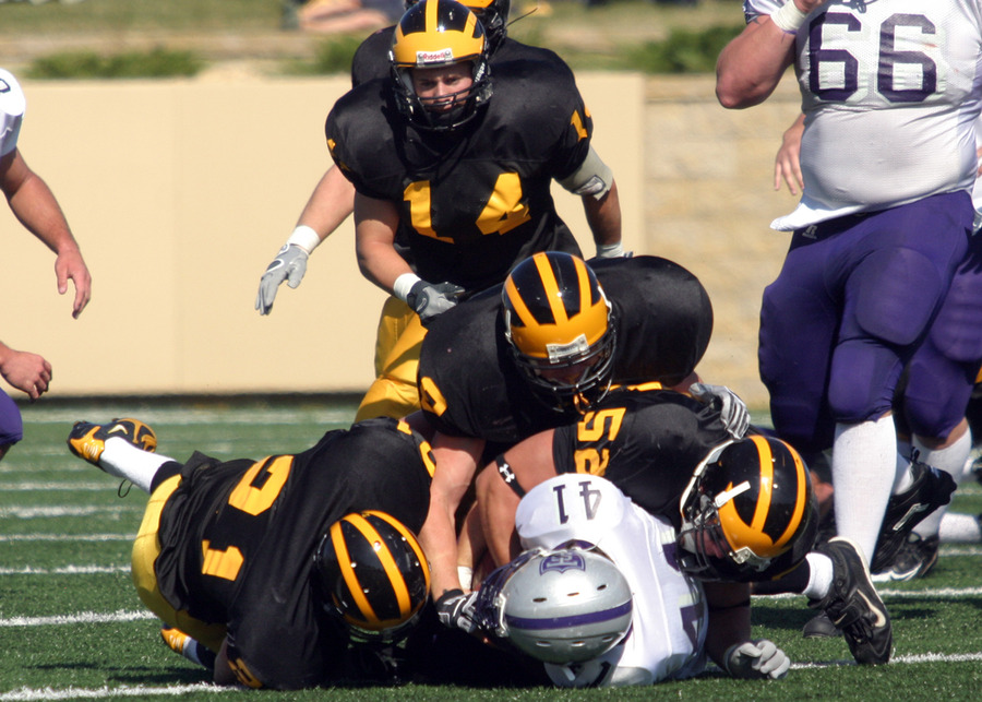 The defense tackles a St. Thomas player.