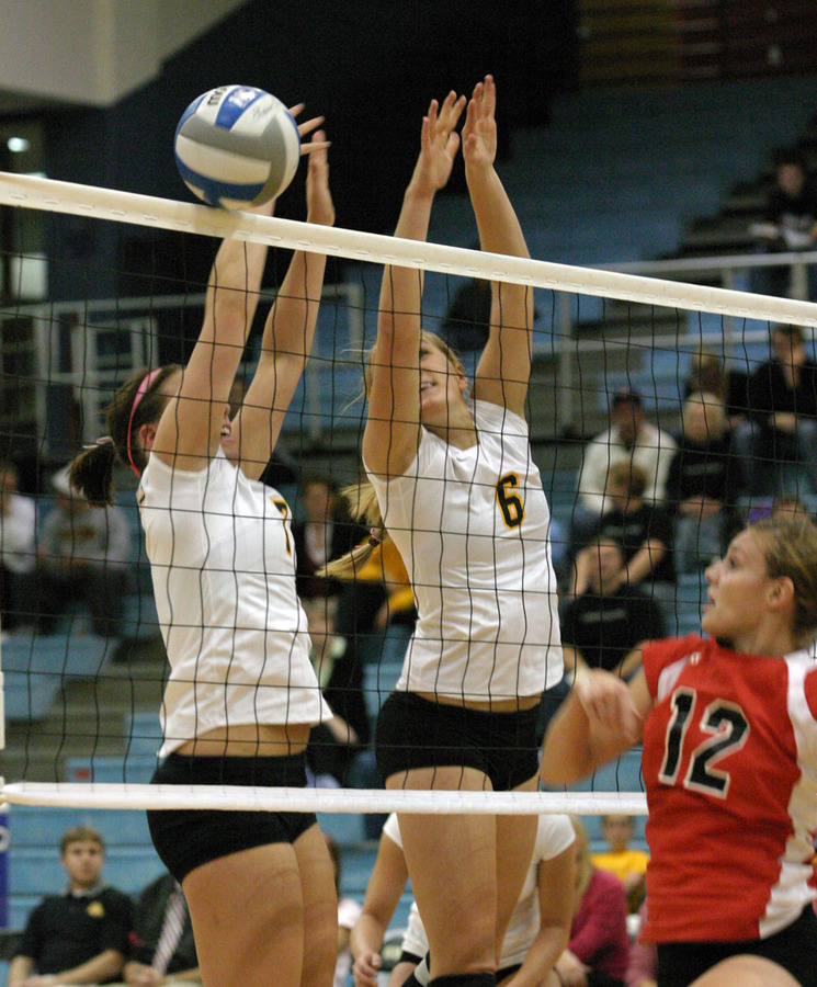 Bridget Burtzel and Meghan Gehring try to block an attack from Emma Jaynes.