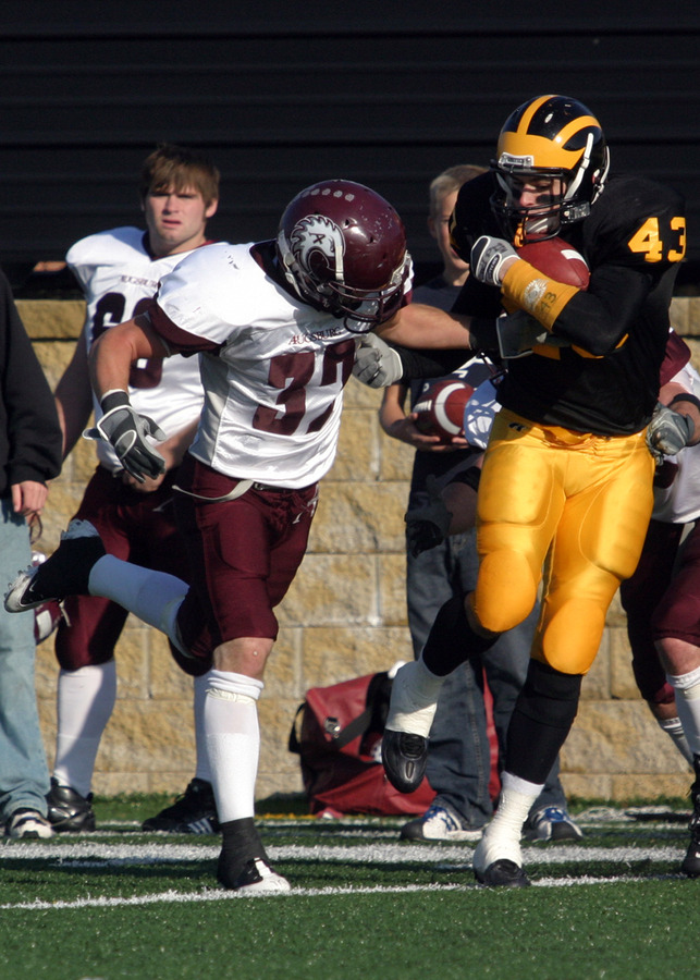 Senior Chad Arlt makes the catch between two Augsburg defenders.