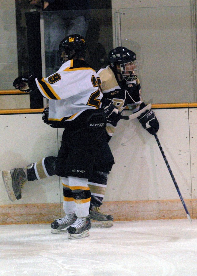 Ryan Noonan checks a Bethel player into the boards.