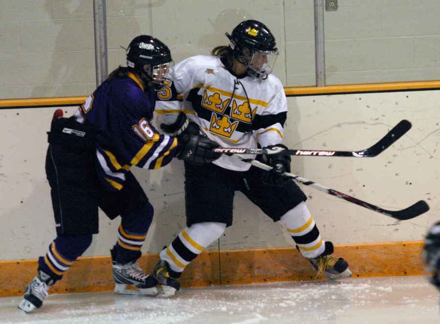 The Gusties' Mari Gunderson battles a Pointer for the puck along the boards.