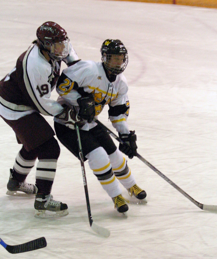 Allie Schwab skates in front of the Auggies Sara Toft in front of the Augsburg net.