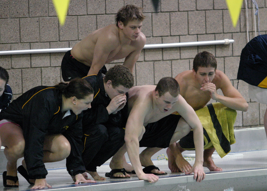 Carrie Gundersen, Ryan Ortlip, Wesley Jones, Jake Kemna (first row), and Kyle Johnsrud (standing) cheer on a teammate.