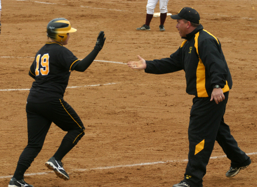 Jenna Johnson celebrates with Coach Annis after hitting a home run in the first game.