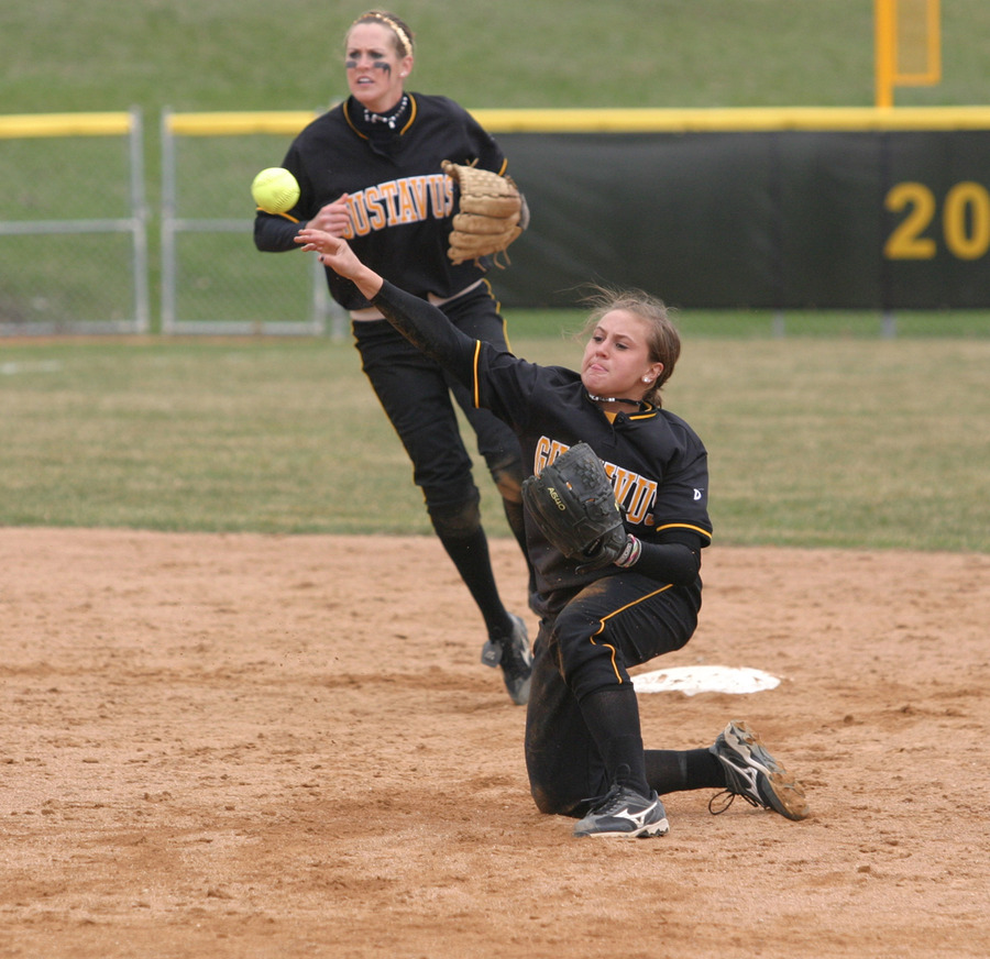 Second baseman Lisa Klass throws out a runner at first base from her knees.