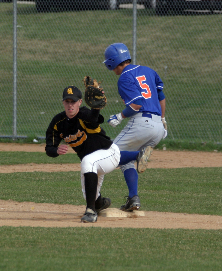 Tory Herman keeps his foot on first base as the throw just beats the Macalester runner.
