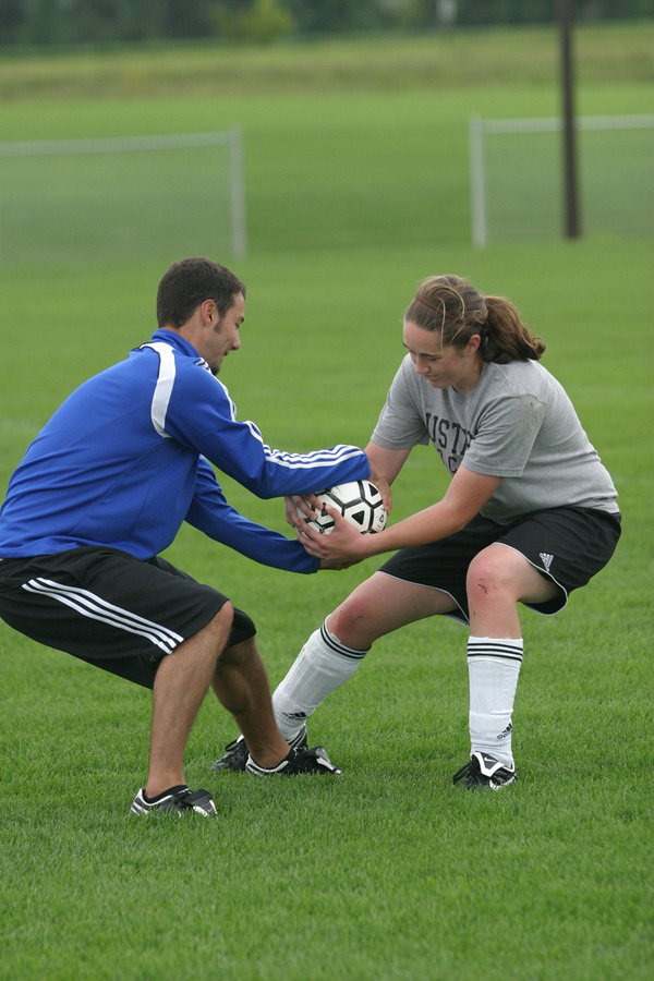 Asst. Coach Dane Obermeyer battles first year goalkeeper Jessica Richert in a tug-of-war drill.