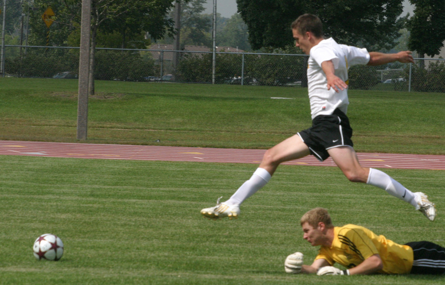 Bret Vander Streek eludes PLU goalkeeper Brian Kostol with an acrobatic move in the first half.