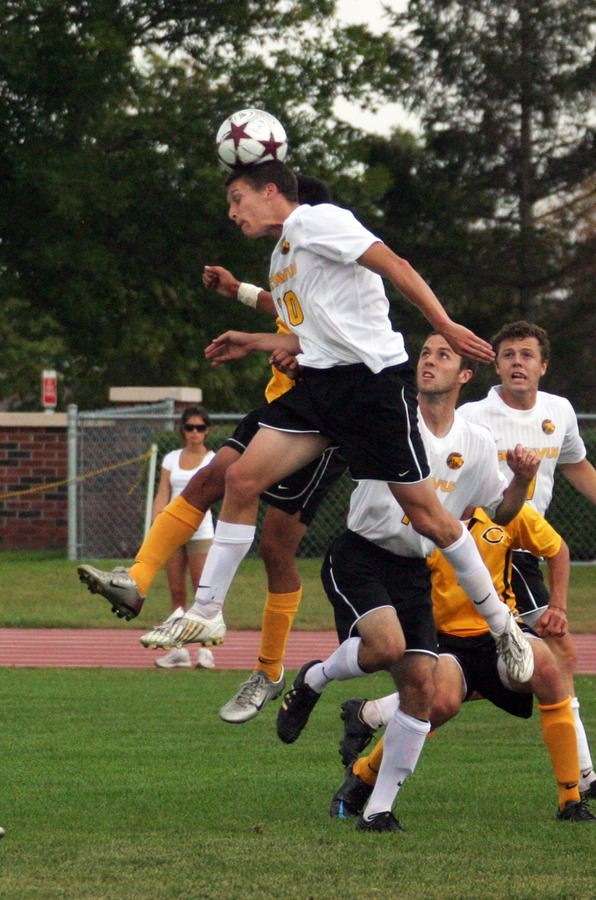 Bret VanderStreek heads a ball to a teammate in front of the goal.
