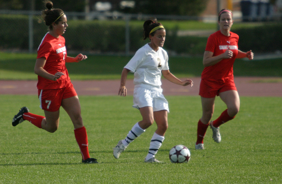 Kirsten Thulien dribbles past two Saint Mary's defenders.